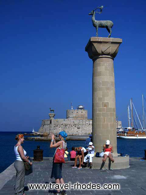 Two girls taking a picture under the deer in the entrance to Rhodes town port RHODES PHOTO GALLERY - RHODES PORT